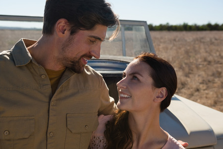 Young couple by off road vehicle looking at each other on landscape