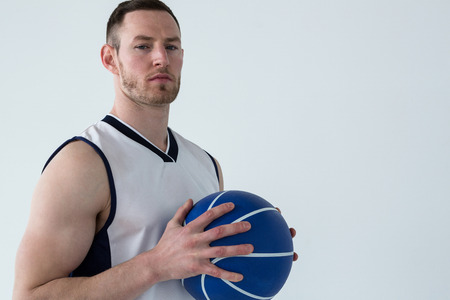 Confident player holding basketball against white background