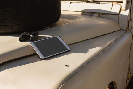 Digital tablet and binocular with spare tire on vehicle hood Lizenzfreie Bilder