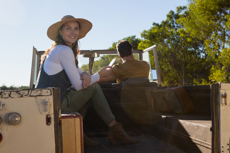 Smiling woman looking away with man driving off road vehicle at forest
