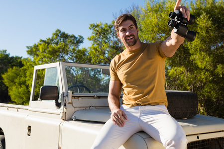 Young man with binocular sitting on off road vehicle at forest