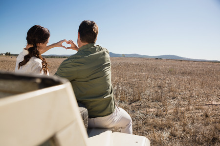 Rear view of young couple making heart shape with hands on off road vehicle at landscape