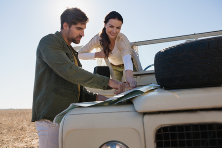 Couple by off road vehicle pointing at map in forest Lizenzfreie Bilder