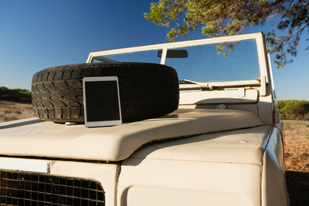 Digital tablet and spare tire on vehicle hood during sunny day