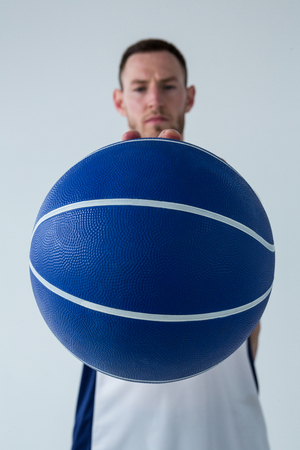Close-up of confident player holding basketball against white background