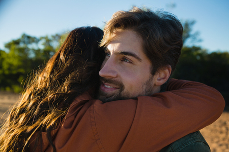 Close-up of young man embracing woman on field