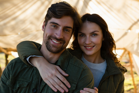 Portrait of smiling young couple standing in tent