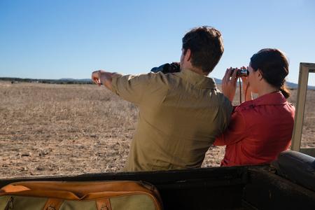 Rear view of couple looking through binoculars against sky at landscape Lizenzfreie Bilder