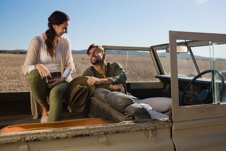 Young couple relaxing in off road vehicle on landscape