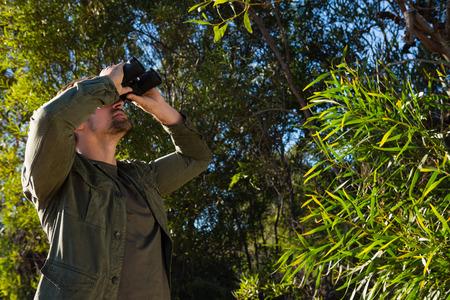 Man looking through binocular while standing by tree Lizenzfreie Bilder