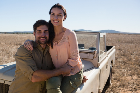 Portrait of smiling woman with man sitting on off road vehicle at landscape