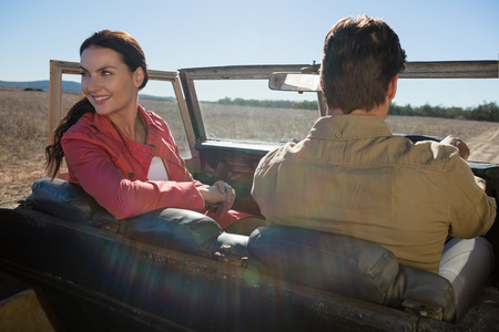 Young woman with man looking away in off road vehicle on landscape
