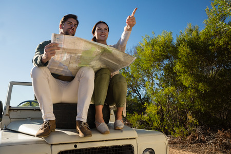 Woman by man with map pointing on off road vehicle with tire at forest