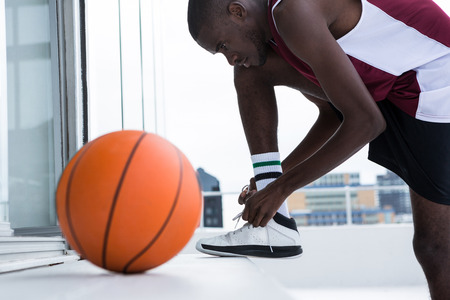 Determined basketball player tying shoelace Stock Photo