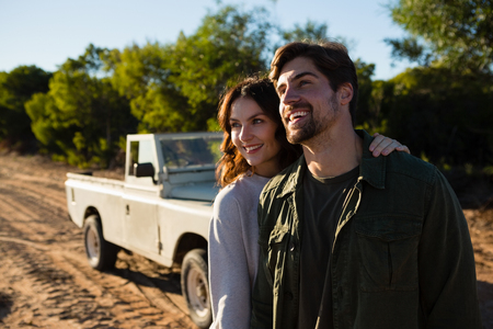 Happy young couple standing by vehicle on field