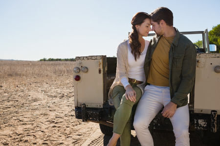 Young romantic couple sitting in off road vehicle at landscape