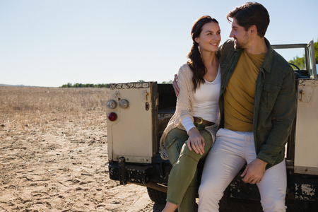 Romantic young couple sitting in off road vehicle on landscape