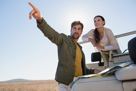 Young man with woman pointing while standing by off road vehicle