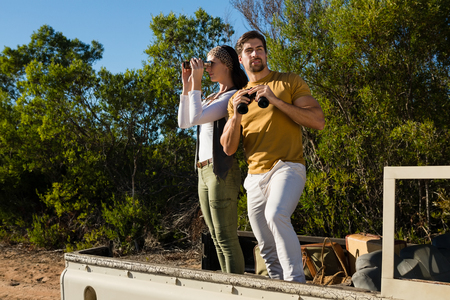 Couple looking through binoculars while standing in off road vehicle at forest