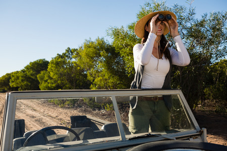 Young woman looking through binoculars standing in off road vehicle against clear sky