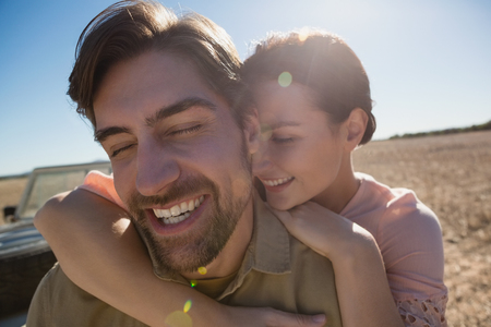 Happy young couple with eyes closed on landscape during sunny day