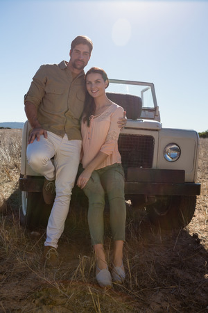 Portrait of young couple by parked off road vehicle on landscape during sunny day Lizenzfreie Bilder