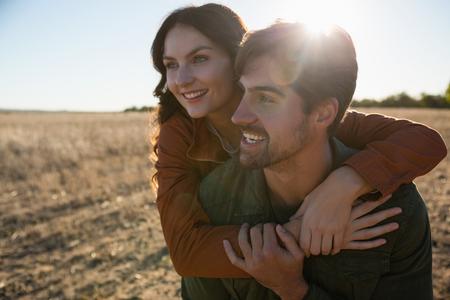 Man giving woman piggyback ride on landscape during sunny day Lizenzfreie Bilder