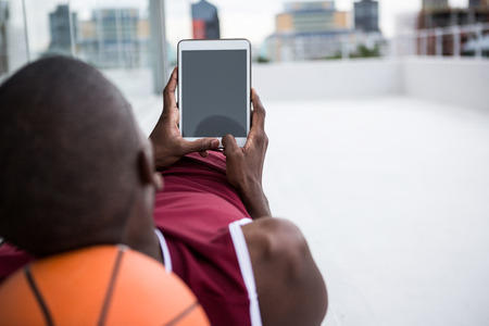 Basketball player using digital tablet while relaxing on terrace