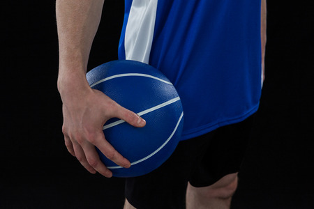 Mid section of player holding basketball against black background
