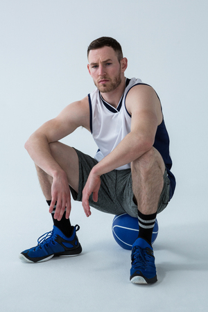 Confident player sitting on basketball against white background