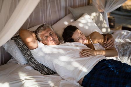 Happy senior couple sleeping on canopy bed