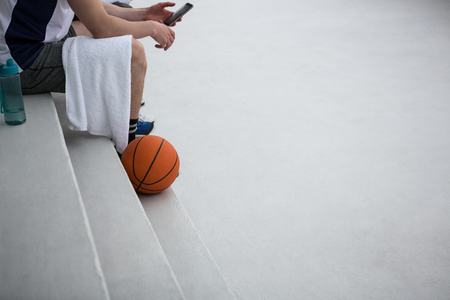 Basketball player using mobile phone on terrace