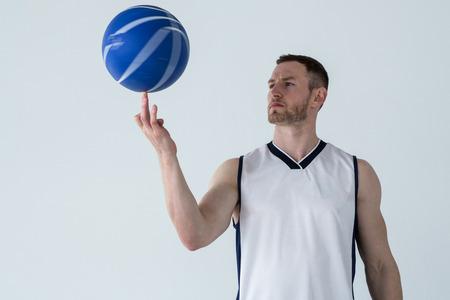 Player spinning basketball on finger against white background