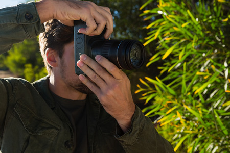 Close-up of young man photographing by tree Lizenzfreie Bilder