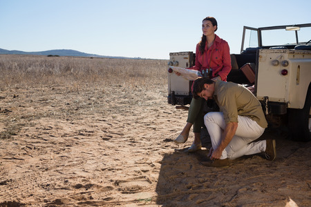 Man with woman tying shoelace by off road vehicle on landscape