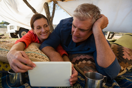 Relaxed mature man with woman looking at tablet in tent