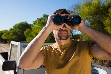 Young man looking through binocular at forest