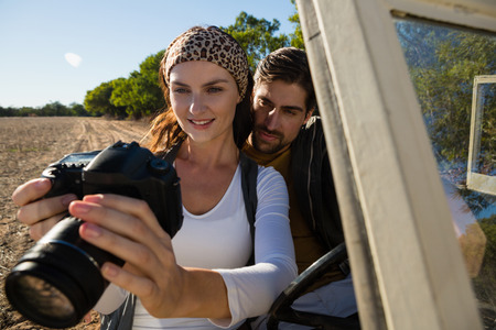 Young couple looking in camera while traveling in off road vehicle at forest Lizenzfreie Bilder