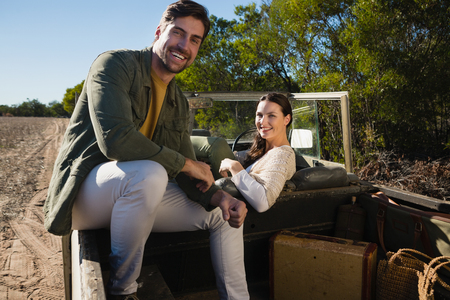 Portrait of smiling young couple sitting in off road vehicle at forest