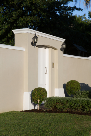 Wall with modern entrance gate on a sunny day
