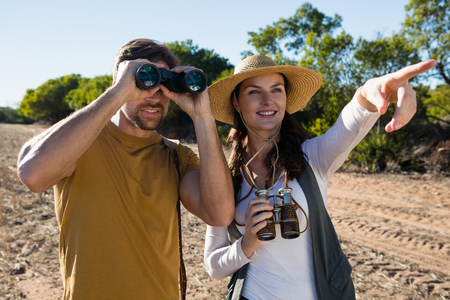 Young couple with binoculars standing at forest Stock Photo