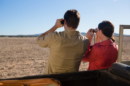 Rear view of couple by off road vehicle looking through binoculars on landscape