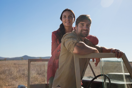 Portrait of couple in off road vehicle against sky on landscape