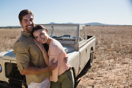 Portrait of happy young couple by off road vehicle on landscape