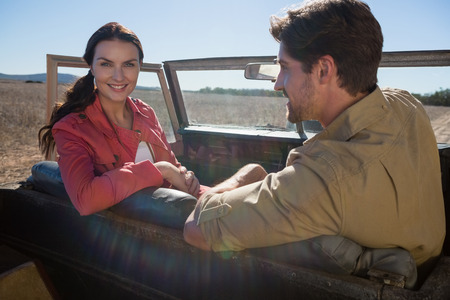 Portrait of woman sitting with man in off road vehicle on landscape Lizenzfreie Bilder