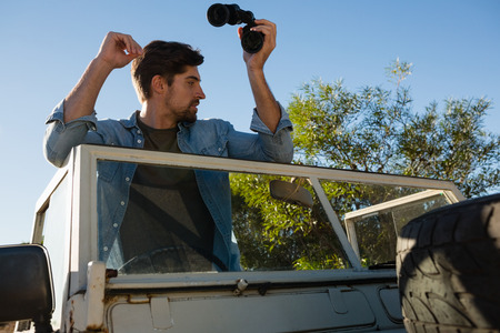 Low angle view of young man holding binoculars looking away while standing in off road vehicle