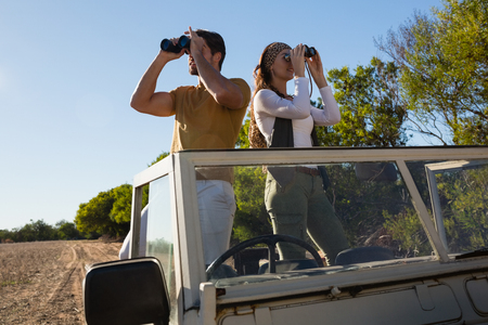 Young couple in off road vehicle looking through binoculars at forest Lizenzfreie Bilder