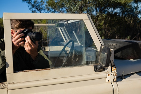 Man photographing from camera while sitting in off road vehicle