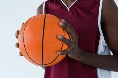 Mid section of player holding basketball against white background