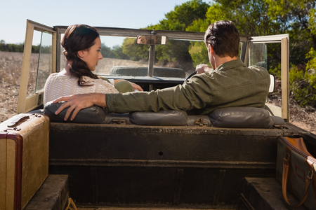 Rear view of man with young woman driving off road vehicle at forest